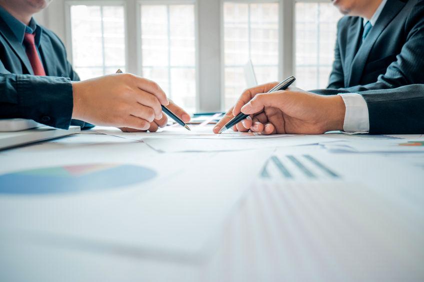 Des hommes d'affaires analysent des statistiques et préconisations financières pour des investissements futurs.