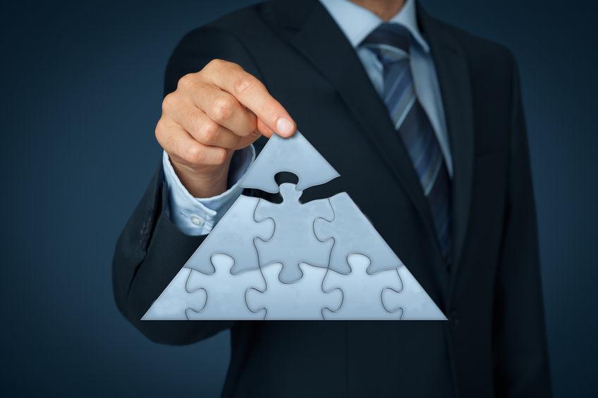 Un conseiller financier reconstitue la structure d'une pyramide qui représente l'entreprise.